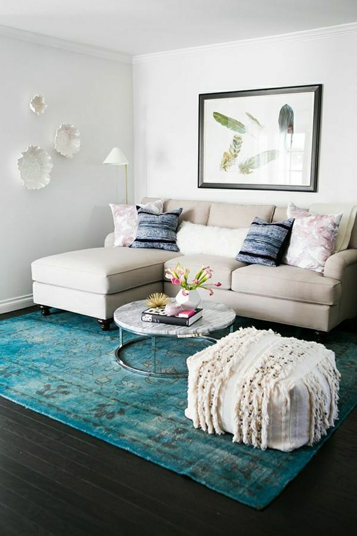 Cream couch with blue overdyed rug via Domino