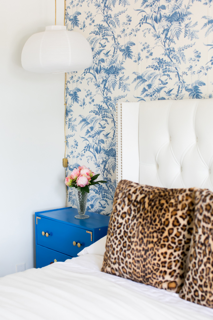 Blue nightstand and white bed