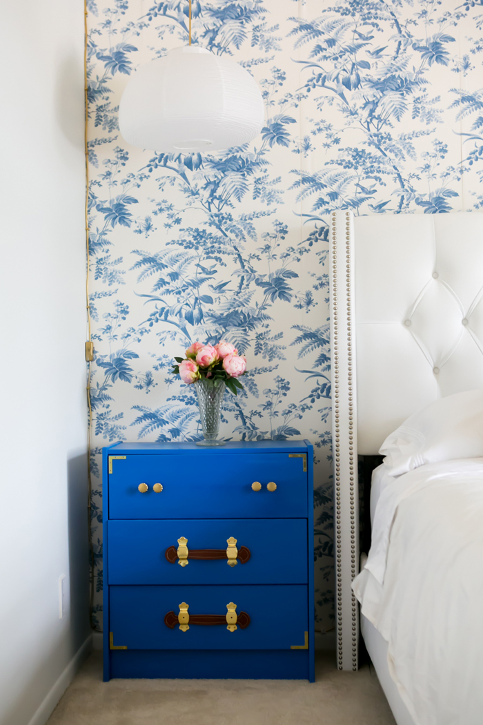 Blue nightstand near white bed