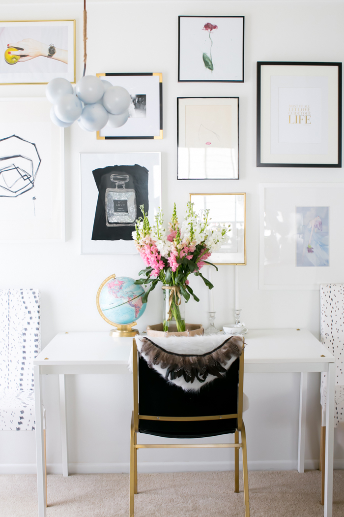 White desk with globe, flowers, and gallery wall