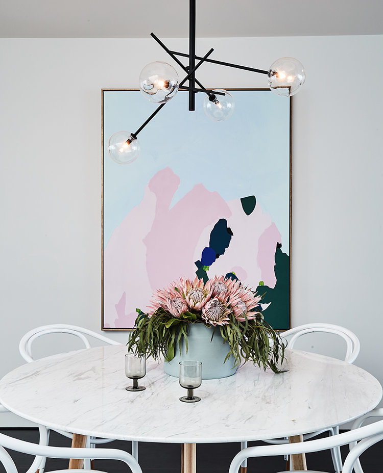Marble dining table with bentwood dining chairs and abstract art via Rebecca Judd Loves