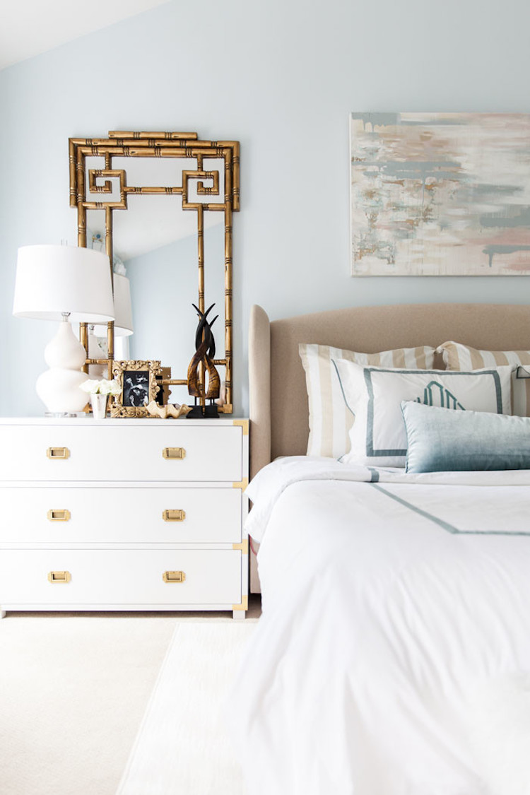 Master bedroom with white table lamp and gold mirror