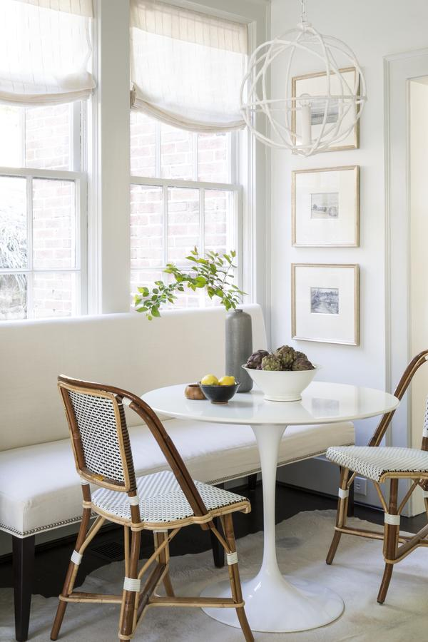 TWo French bistro chairs at white tulip table breakfast nook with bench