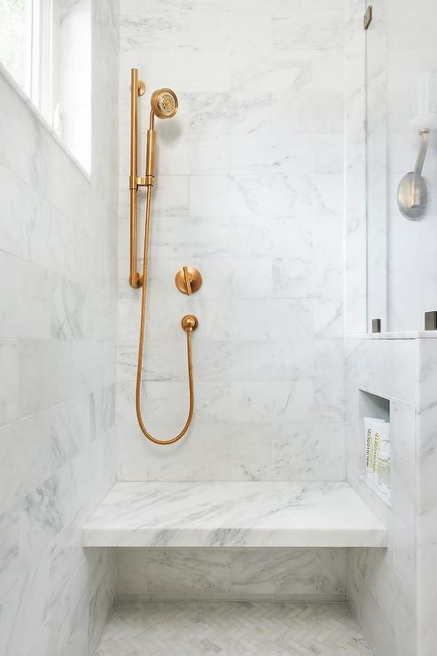 Brass Fixtures in a Marble Shower with Seat