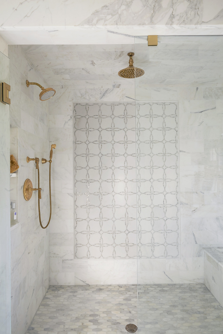 Brass Fixtures in a Walk-in Marble Shower