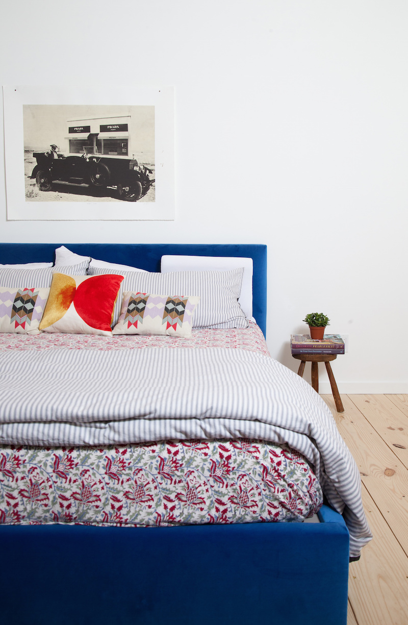 Claire Zinnecker Blue bed with Prada marfa artwork