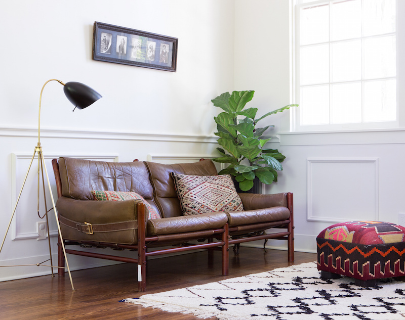 Claire Zinnecker Brown Leather couch with rug and poof
