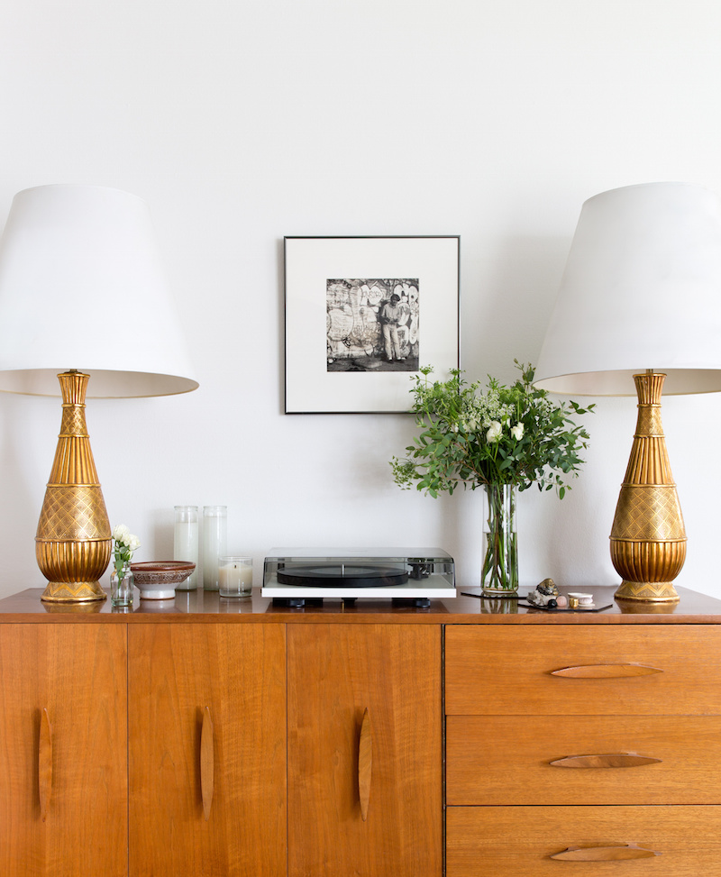 Claire Zinnecker Brown sideboard with gold lamps