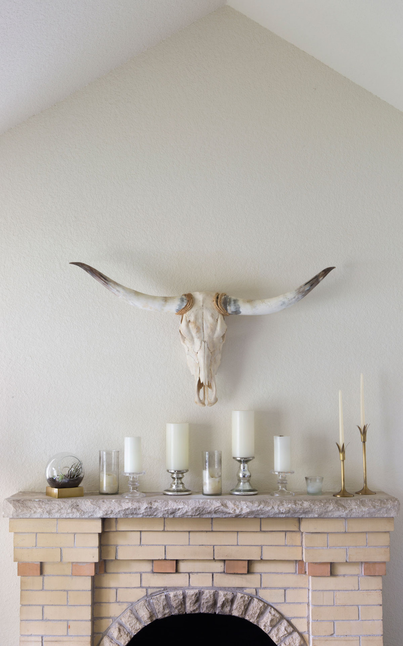 Claire Zinnecker Fireplace with white candles and bull skull taxidermy