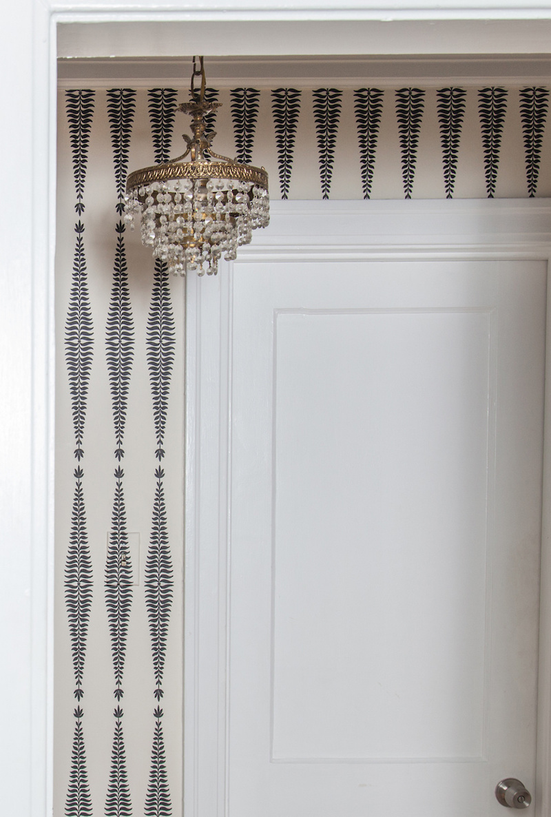 Claire Zinnecker Vintage chandelier with black and white wallpaper