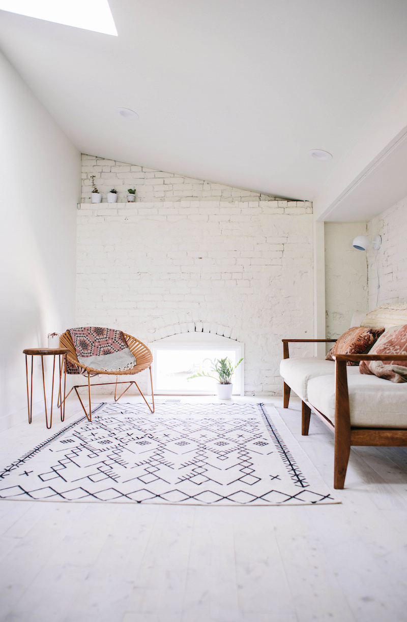 Claire Zinnecker White couch against brick wall