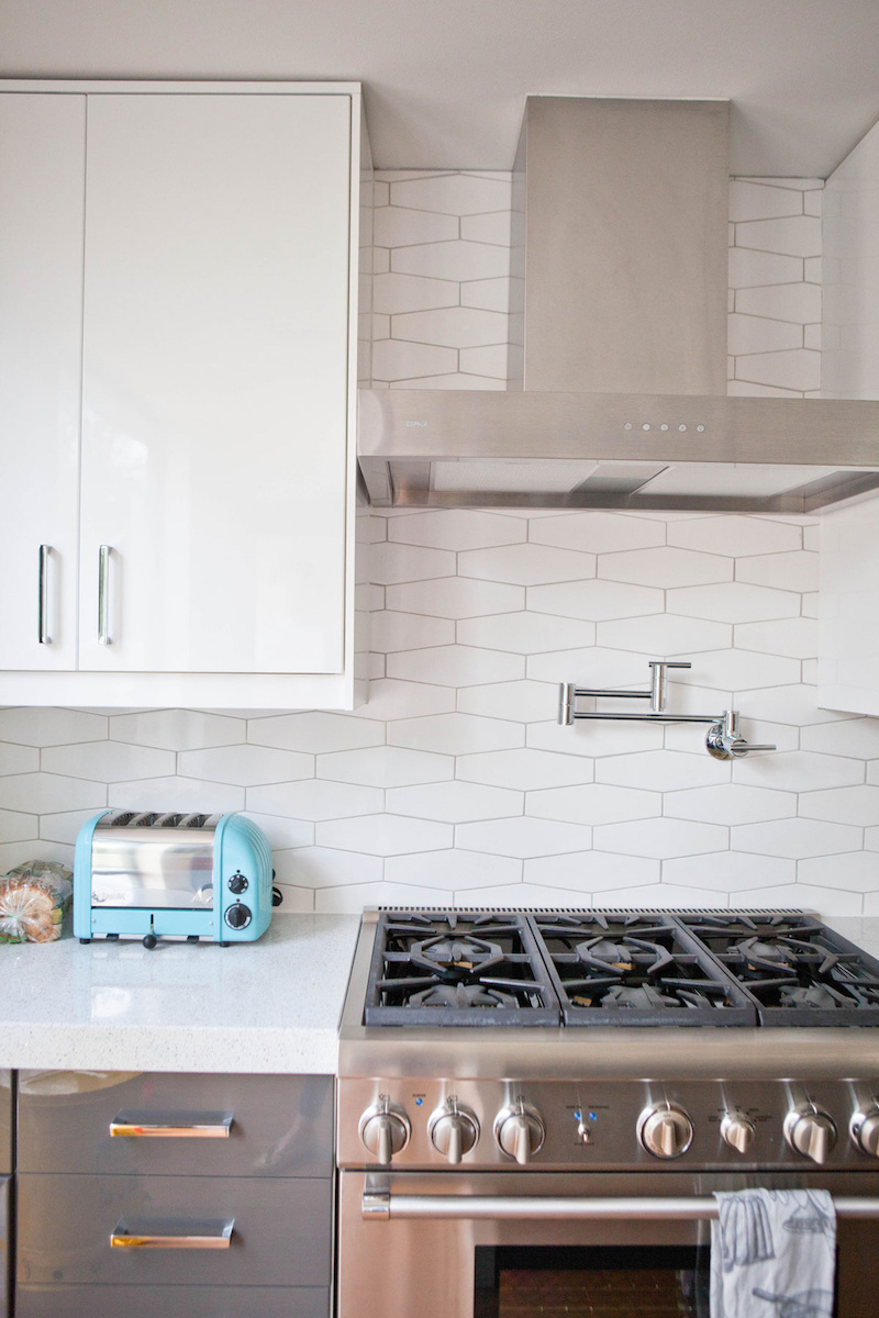 Claire Zinnecker White tile kitchen with silver stove