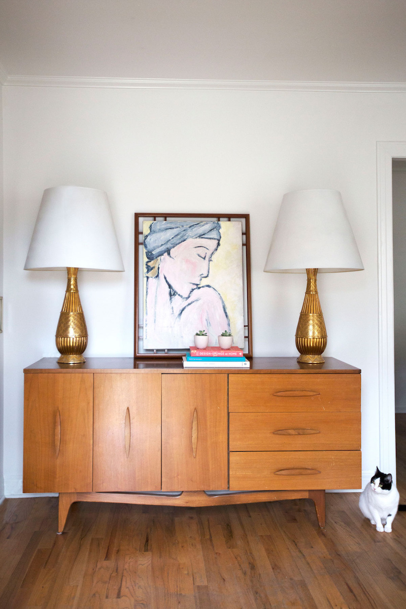 Claire Zinnecker Wooden sideboard and golden lamps with art