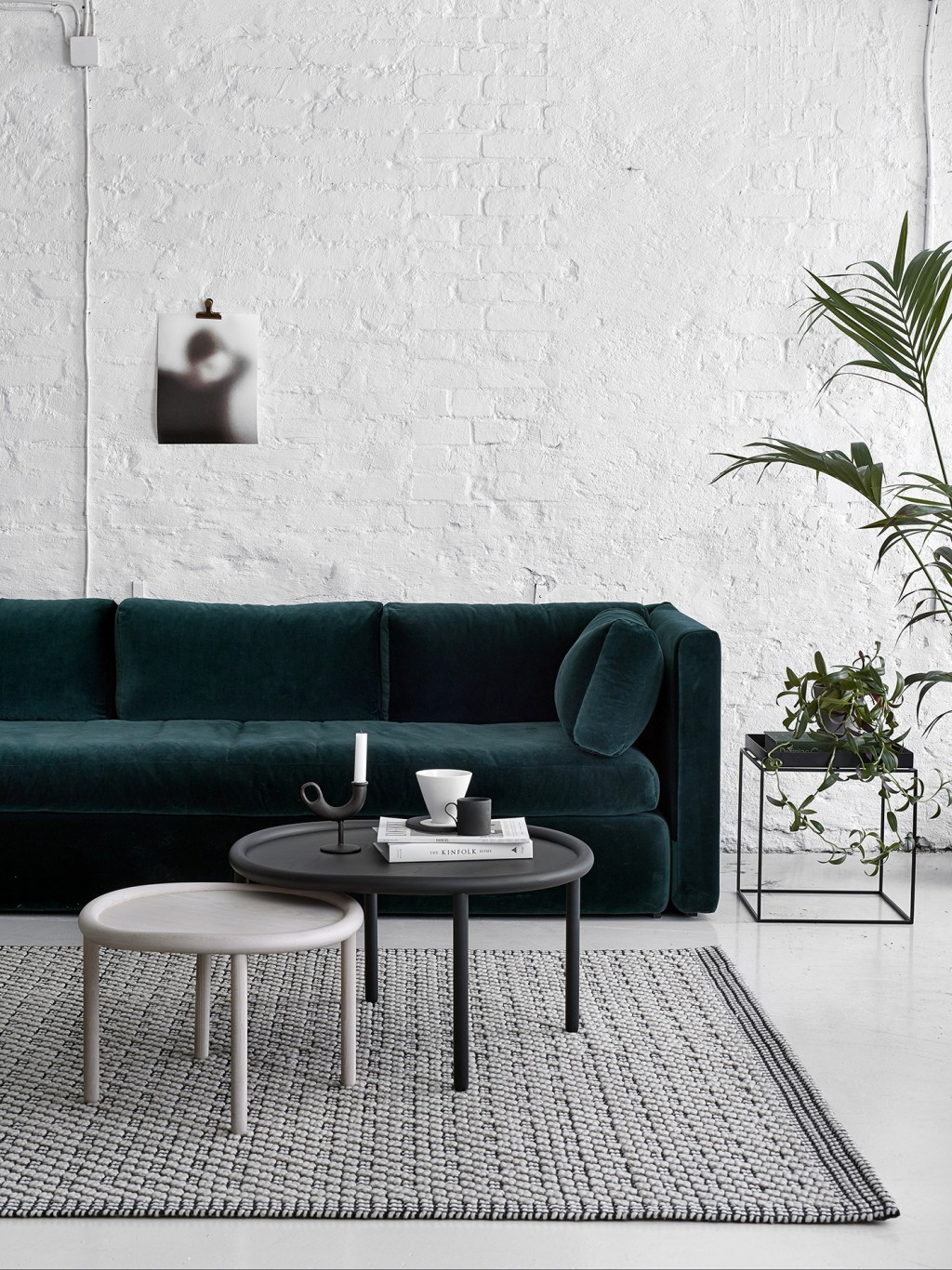 Dark green velvet sofa against white brick wall