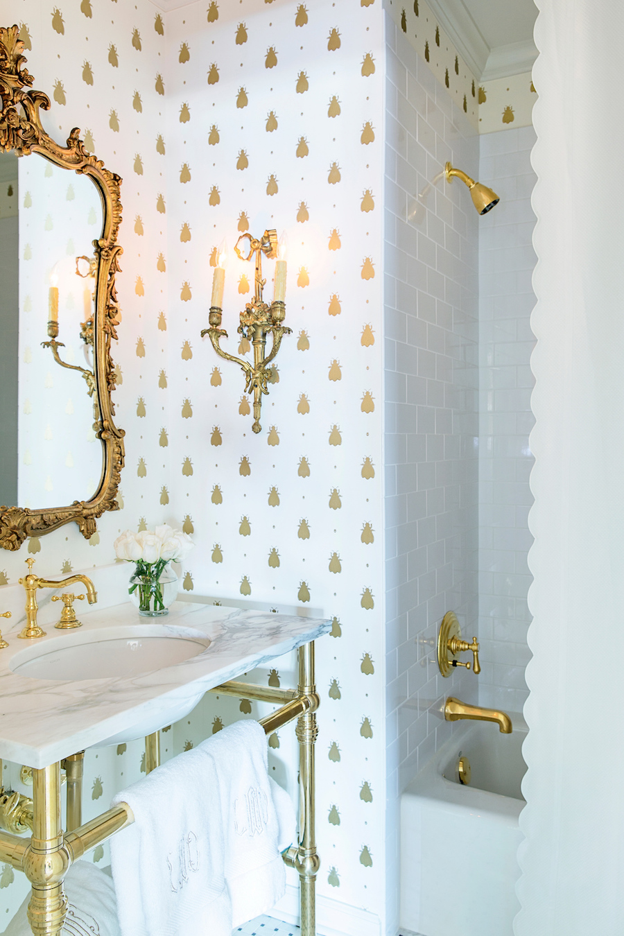 Gold fixtures in marble bathroom with gilded mirror and spotted wallpaper