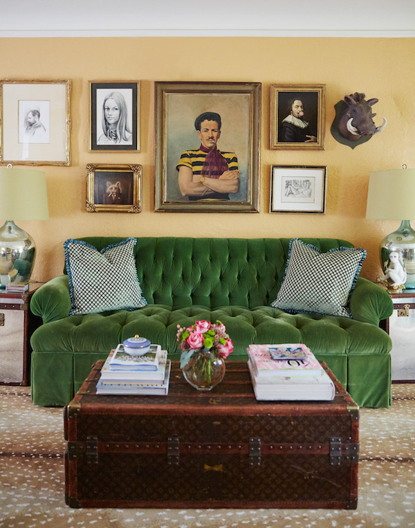 Green velvet tufted sofa with louis vuitton trunk and portrait painting