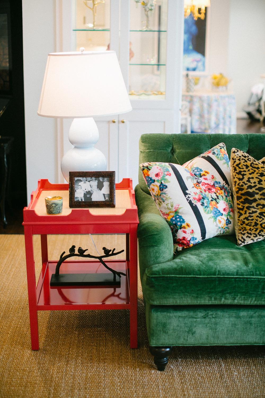 Green velvet sofa with red side table