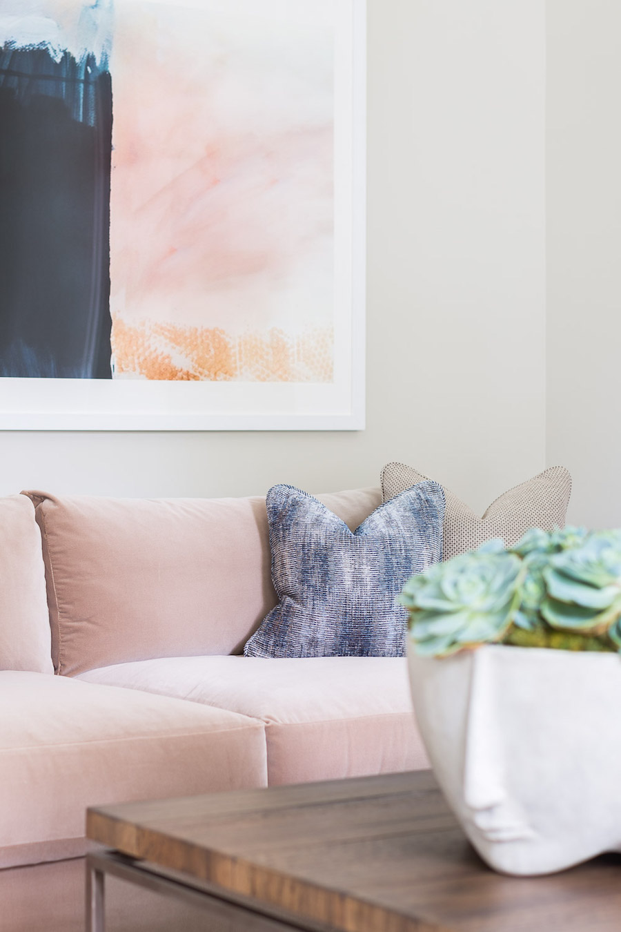 Pink couch and artwork in a Living Room by Amanda Barnes