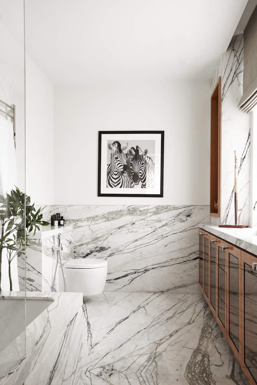 Marble Bathroom with Brown Cabinets and Zebra Art