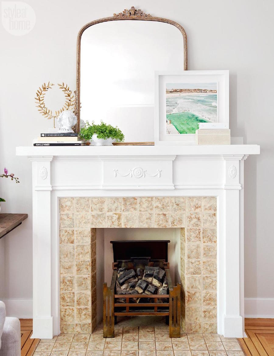 White fireplace with vintage french mirror in this Parisian Inspired Apartment