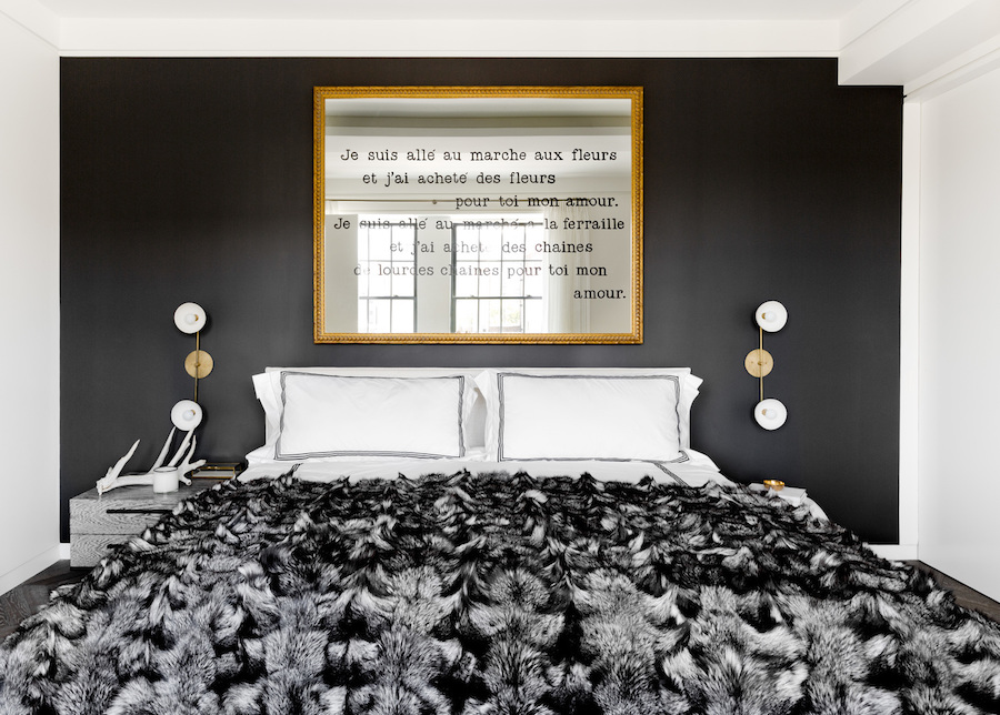 Bedroom with black accent wall and fur throw