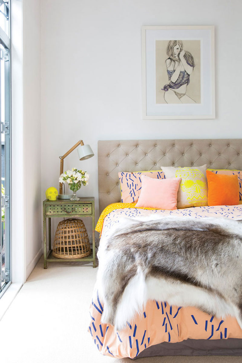 Bedroom with peach orange and yellow throw pillows