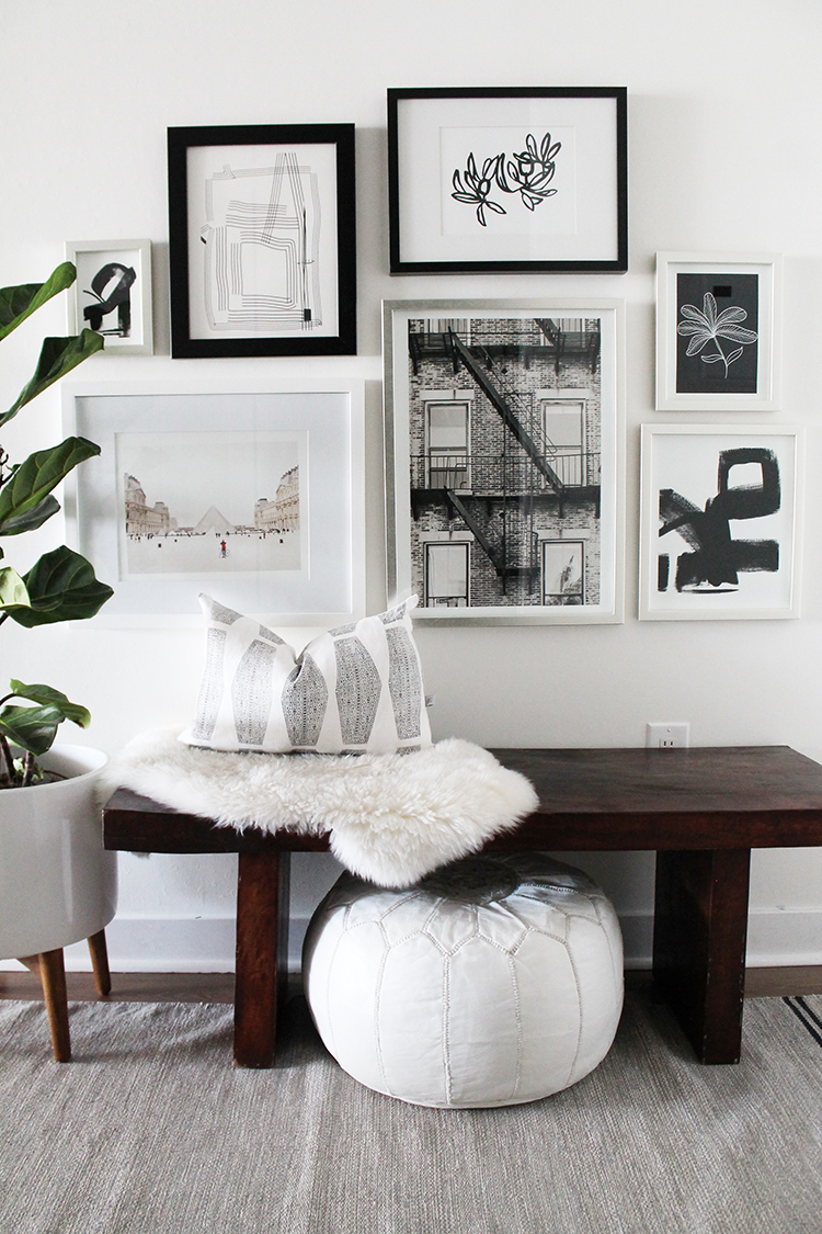 Black and white Gallery wall entryway with dark wood bench