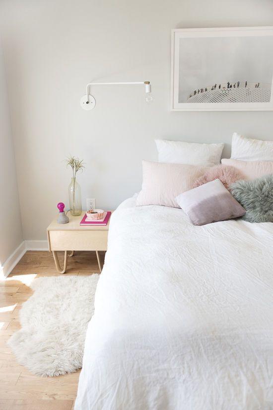 Blush throw pillows on a white bed