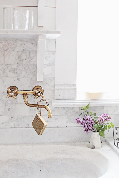 Brass kitchen sink fixtures with marble backsplash