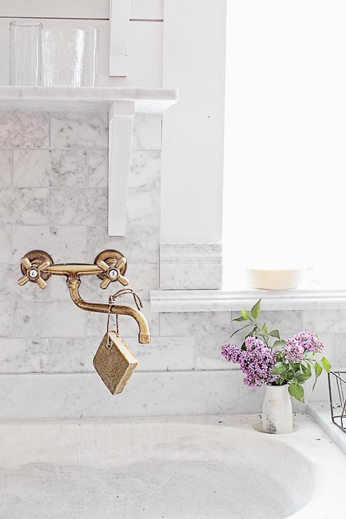 Brass kitchen sink fixtures with marble backsplash