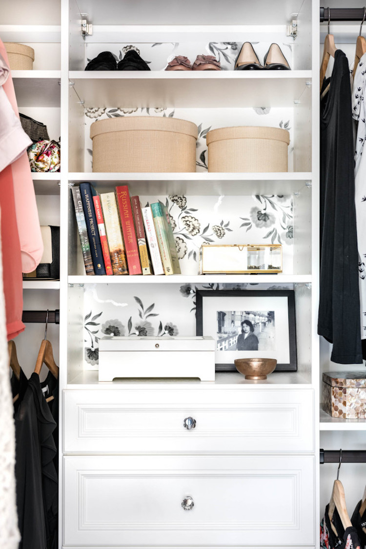 Closet with white shelves and wallpaper behind