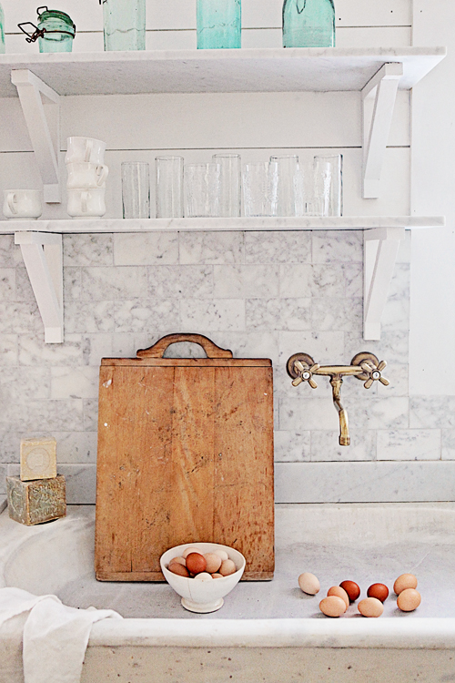 Eggs and wooden cutting board in French sink marble backsplash