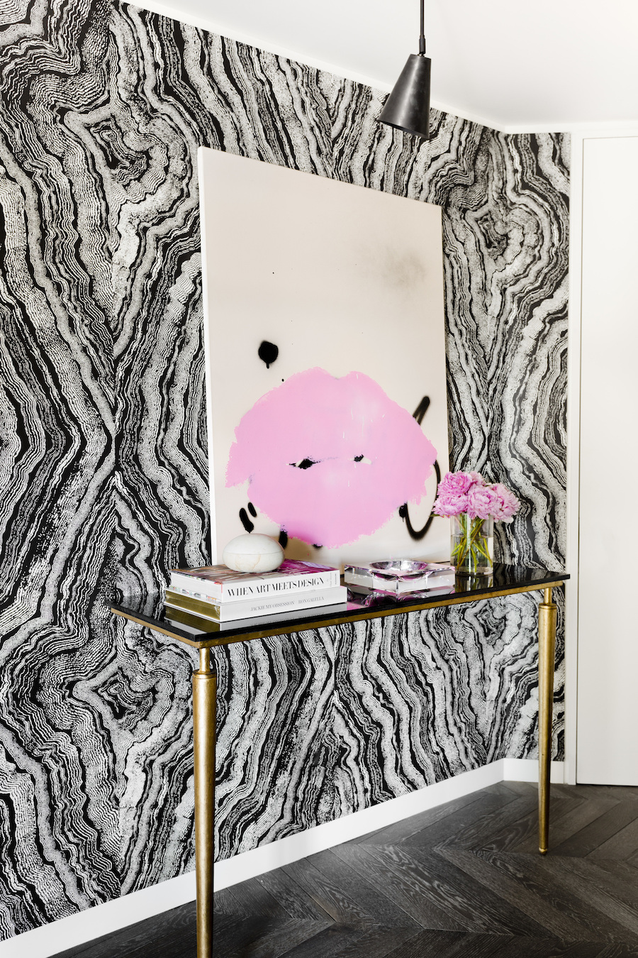 Entryway with black and white wallpaper and bold pink artwork