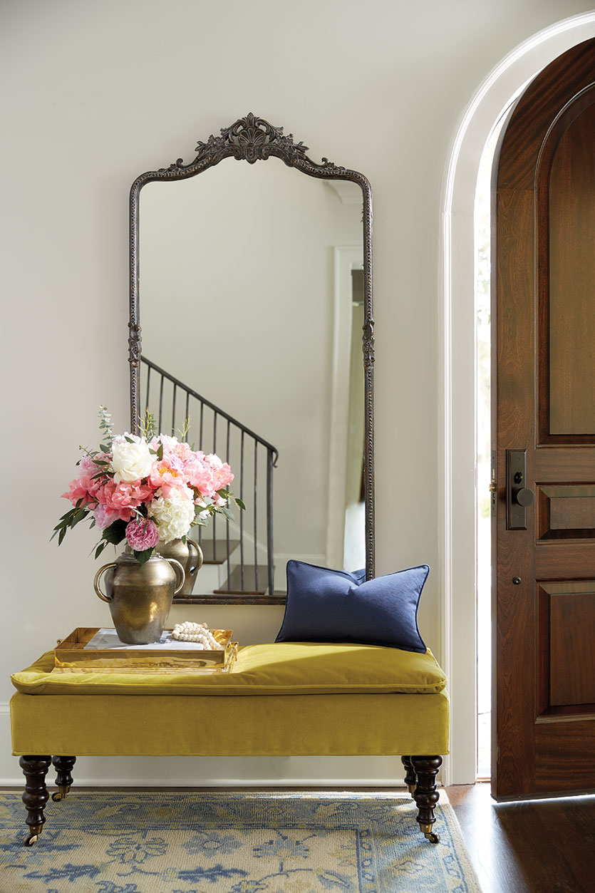 Entryway with mustard yellow bench under mirror