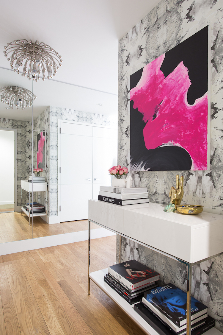 Entryway with white console table, pink artwork and silver pendant light via Homepolish