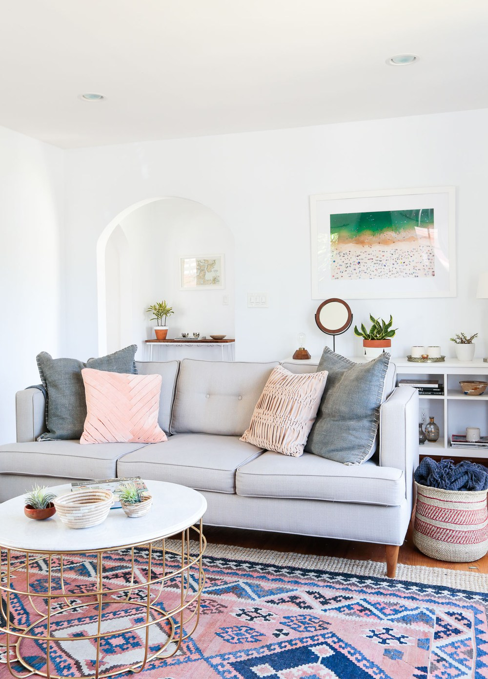 Grey sofa with pillows and pink patterned rug