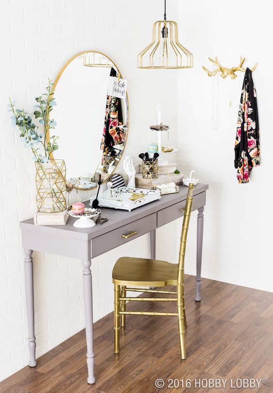 Grey vanity with gold mirror and chair