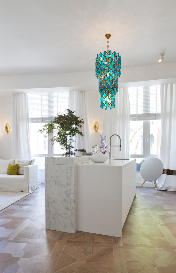 Marble island kitchen with turquoise chandelier, design by Beatriz Silveira