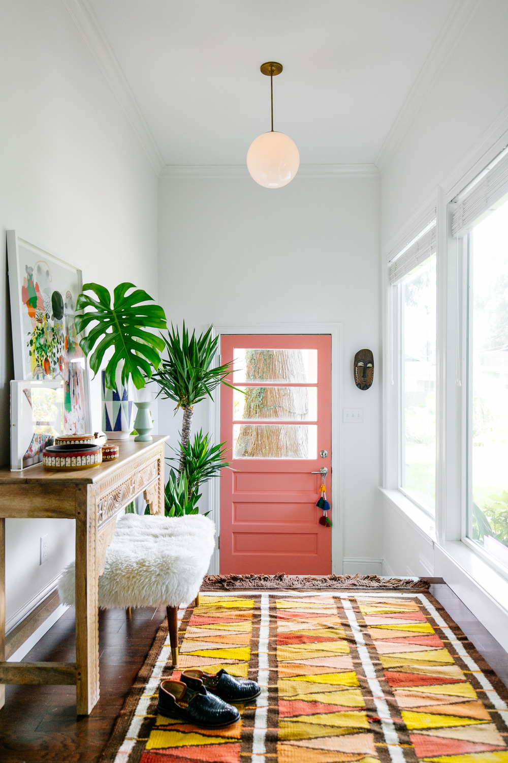 Peach door with orange rug Entryway via Old Brand New