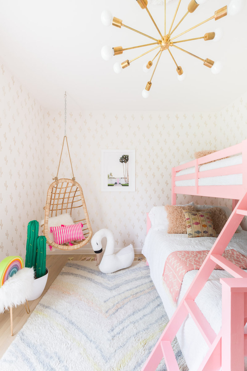 Pink bunk bed kids room with hanging wicker chair