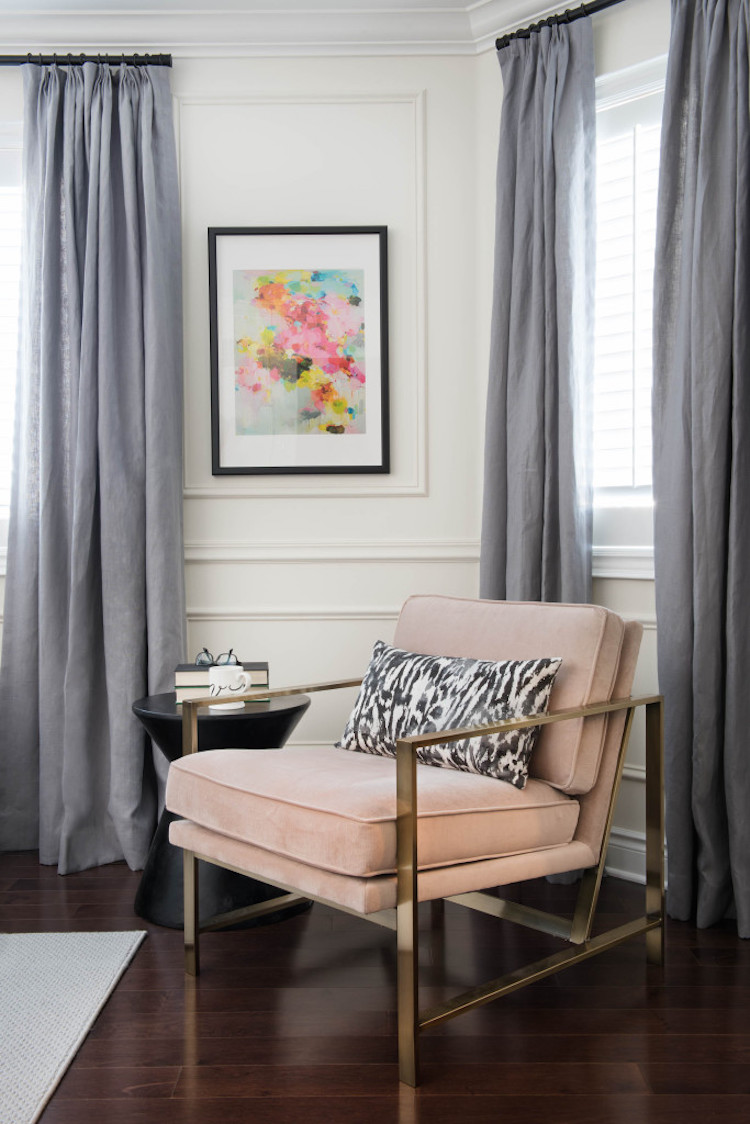 Pink chair in front of grey curtains