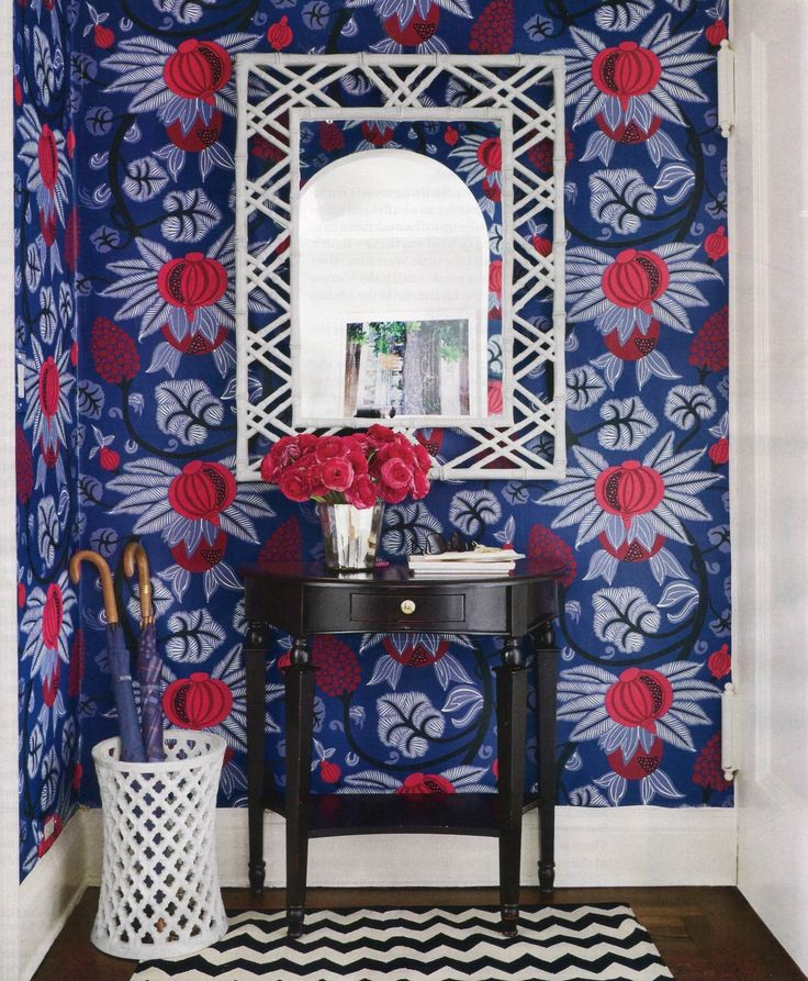 Red and blue wallpaper with black sidetable Entryway