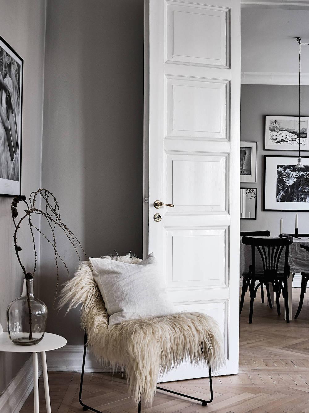 Scandinavian Black chair with fokati throw against dark grey wall