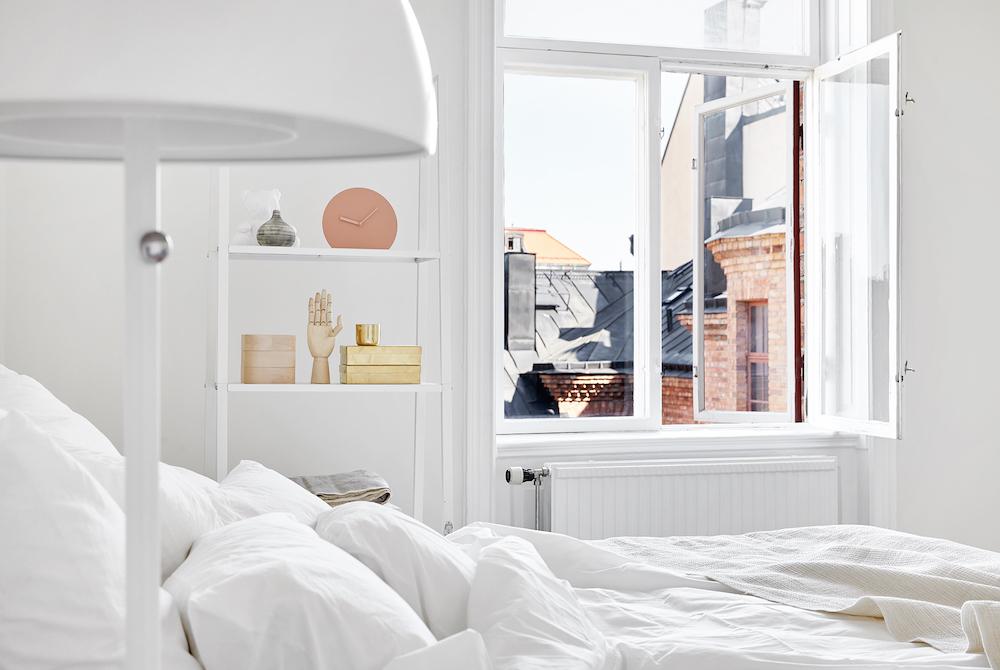 Scandinavian bedroom with minimalist sculptures on shelves