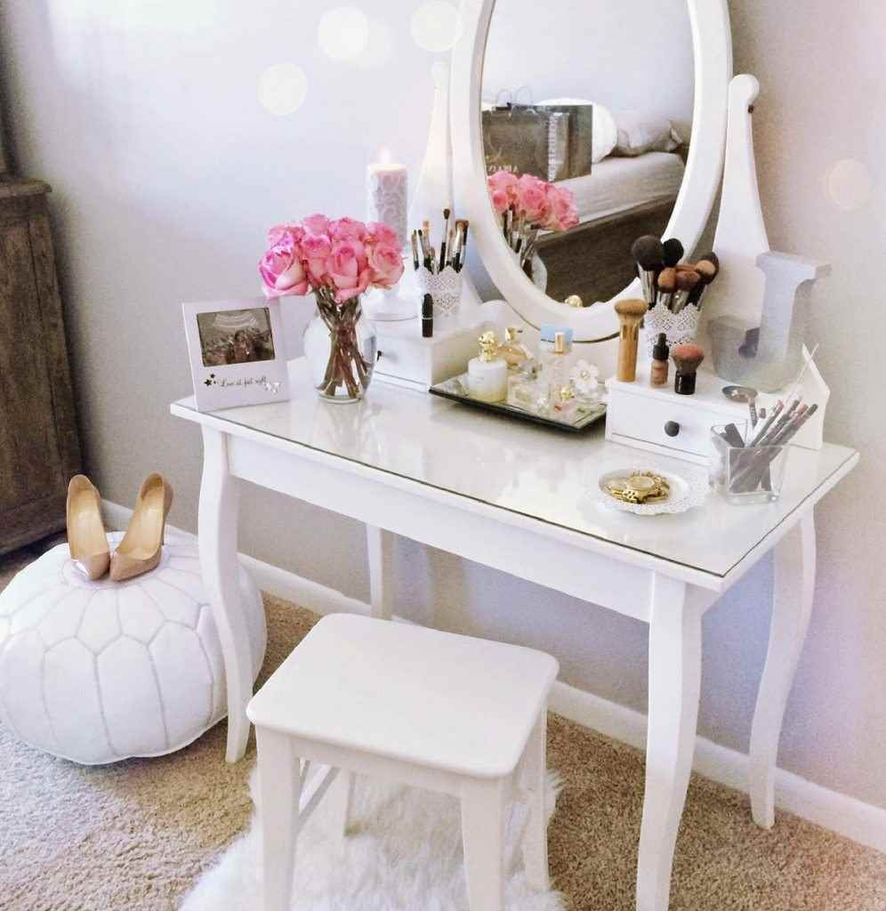 Small white vanity with pink flowers and white poof