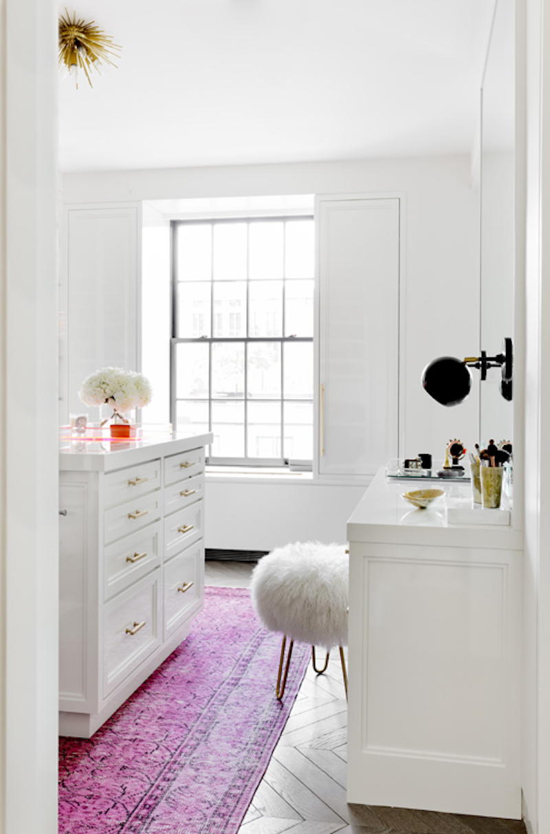 Vanity space with pink rug and fur stool
