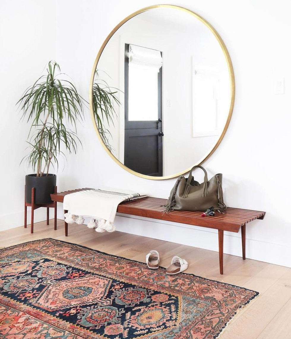 Vintage Rug interior with wood bench and oversized mirror via Amber Interiors