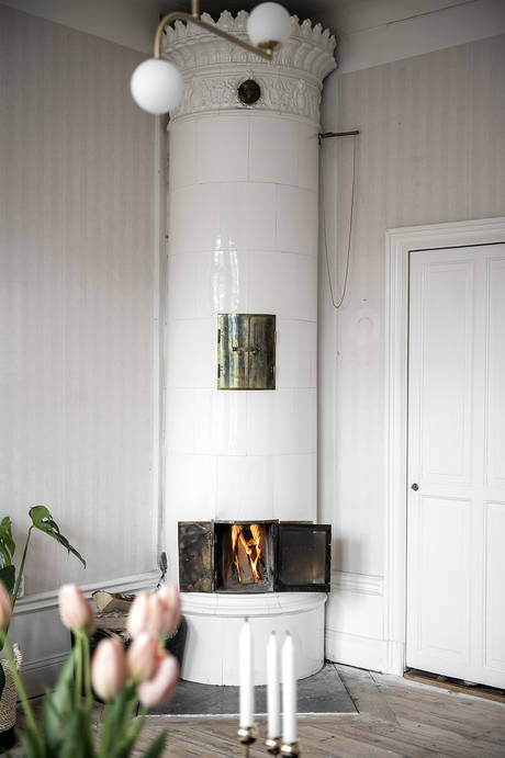 Vintage white fireplace in Swedish living room