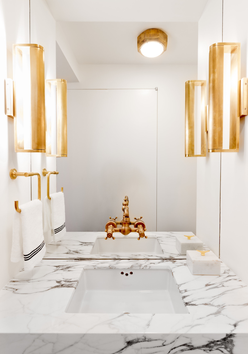 White Marble bathroom with gold faucet and twin lights