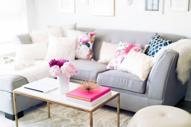 White and gold coffee table with flowers and a grey couch
